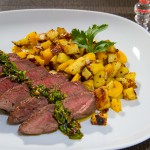 Rosa gebratenes Rindersteak mit Chimichurri und mediterranen Kartoffelwürfeln